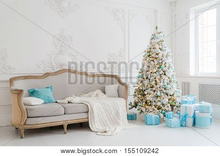 Stylish Christmas interior with an elegant sofa. Comfort home. Christmas tree with presents gifts underneath in living room.