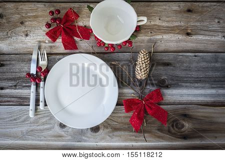 horizontal image of a christmas dinner place setting with white plate and cup adorned with bows and twigs  on an old rustic wood background.