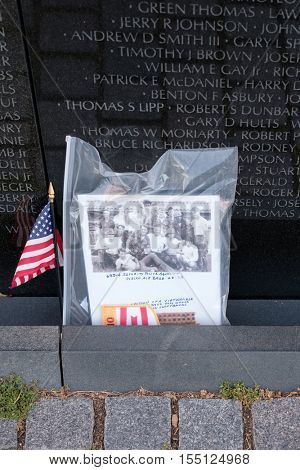 WASHINGTON D.C.,USA - AUGUST 14,2016 : Photograph and american flag left as tributes at the Vietnam Veterans Memorial in Washington D.C.