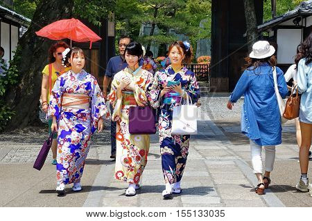 Kyoto,Japan-June 25,Three women's kimonos come back  after  Buddha respect at  Fushimi Inari Shrine  on June 25,2016 in Kyoto,Japan. Selective focus at wowen.