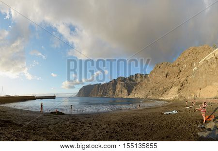 LOS GIGANTES, CANARY ISLANDS, SPAIN - OCTOBER 05: Tourists are visiting Guios beach near port entrance at foot of Gigantes cliffs in light of sunset on October 05, 2014 in Los Gigantes, Tenerife Island, Canary Islands, Spain.