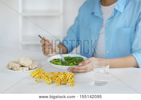 Woman eating salad and measuring tape on table