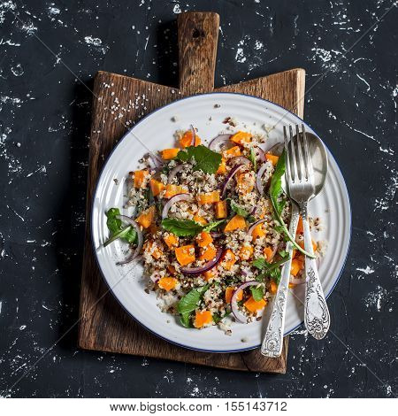 Salad with quinoa and roasted pumpkin. On a dark background top view