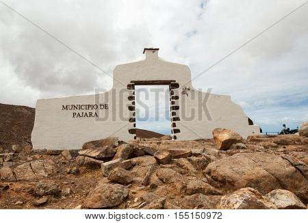 Typical municipality sign (white arch gate) near Pajara with desert mountain landscape in the background Fuerteventura Canary Islands Spain