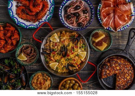 Typical spanish tapas concept. Concept include slices jamon bowls with olives anchovies spicy potatoes mashed chickpeas shrimp calamari manchego with quince marmalade pans with tortilla paella mussels on a wooden table.