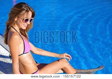 Beautiful young woman sitting on edge of swimming pool