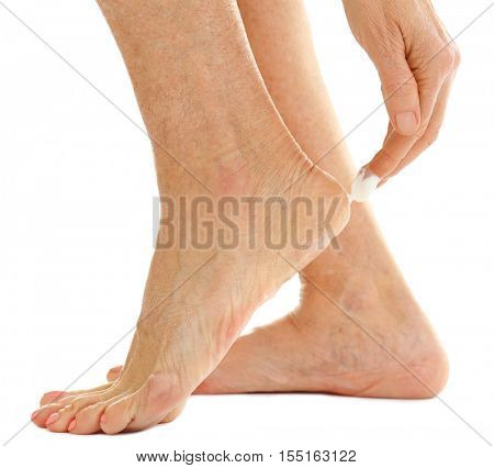 Female hand applying cosmetic cream on heel, closeup