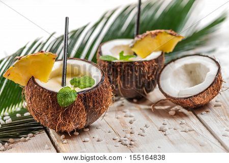 Pinacolada in the coconut with pineapple on old wooden table