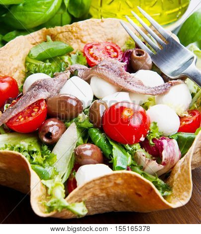 Mixed Salad With Mozzarella And Anchovy In A Bread Basket