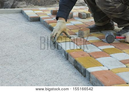 Laying Paving Slabs by mosaic close-up. Road Paving construction. Repairing sidewalk. Worker laying stone paving slab. Laying colored tiles in a city park (garden). Hand fixed tessellated sidewalk tile