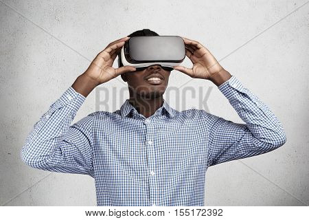 Technology innovation and cyberspace concept. Amazed African employee in blue shirt having fun and entertaining himself while playing video games in office during break using oculus rift headset