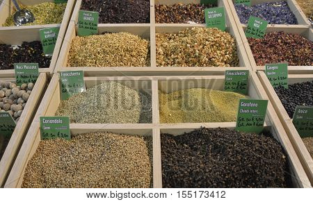 A selection of died ground spices on an Italian spice market stall - dried orange petals fennel seeds coriander seeds dried jasmin petals dried fennel petals and cloves. The focus is on the centre of the display.