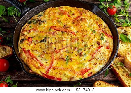 Frittata made of eggs, potato, bacon, paprika, parsley, green peas, onion in iron pan. on wooden table