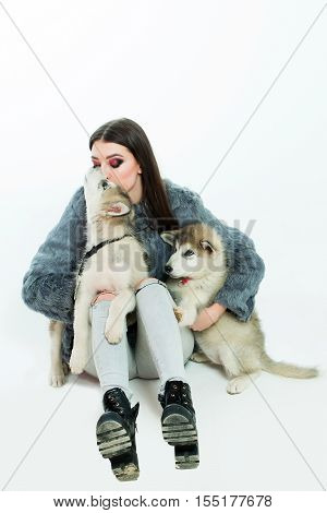 pretty sexy brunette woman or girl with long hair and fashion makeup in fur coat with cute little dogs or puppy of husky pet isolated on white background