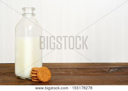 bottle of milk with cookies on wood table