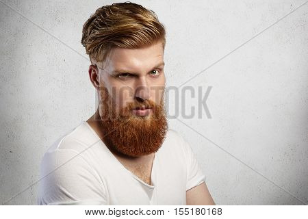 Studio Shot Of Handsome Fashionable Man With Long Red Beard And Trendy Hairstyle Having Serious And