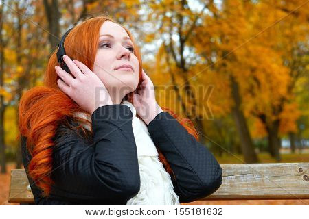 girl listen music on audio player with headphones, sit on bench in city park, autumn season, yellow trees and fallen leaves