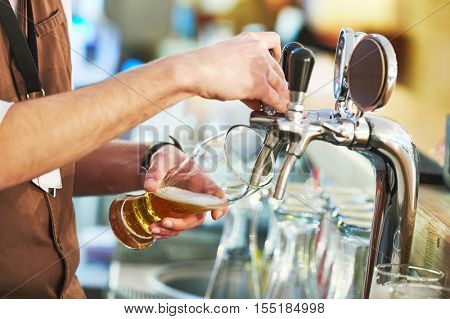barman hand at beer tap pouring a draught lager beer