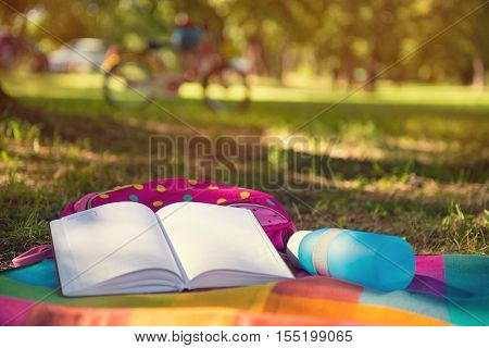 In summer park lying on blanket book rucksack and bottle. Bicycle on background