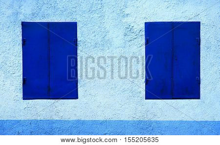 Two blue windows with iron shutters closed in the blue stone house.