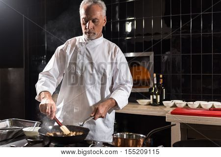 Restaurant kitchen. Involved concentrated bearded chef mixing mushrooms on the frying pan while standing near the stove in the kitchen of the restaurant and holding the spatula
