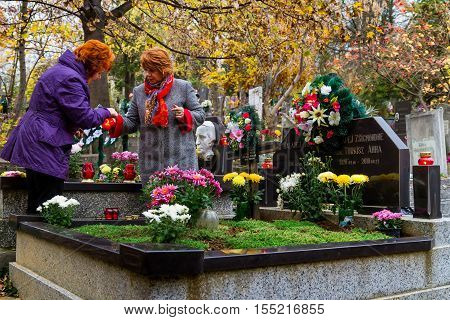 Uzhgorod Ukraine - November 1 2016: Women set fire to candles in memory of deceased relatives graves on the Day of All Saints. On this day the locals decorate the graves with flowers and burning candles of memory.