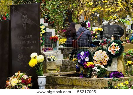Uzhgorod Ukraine - November 1 2016: Young family sitting at the grave of the dead relatives in the celebration of All Saints' Day. On this day the locals decorate the graves with flowers and burning candles of memory.