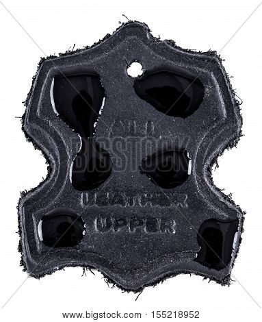 Real leather label in black with water drops on to show water resistance. Isolated on a white background