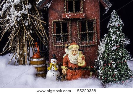 arts and crafts miniature scene of rustic house in deep snow with Christmas tree, Santa, and snowman
