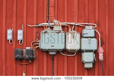 Retro styled junction boxes on a red wall