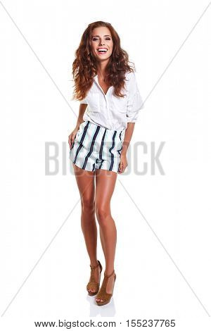Full length of smiling young slim tanned female in denim shorts shrugging her shoulders, isolated on white background