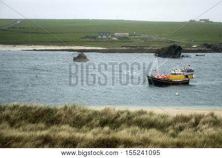 Orkney island Scotland scapa bay boat in front of sunken rusty ship wreck