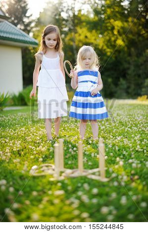 Two Cute Little Sisters Playing Ring Toss Game Outdoors