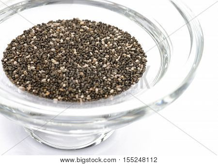Chia seeds Selective focus in a thick round glass bowl on a bright white background