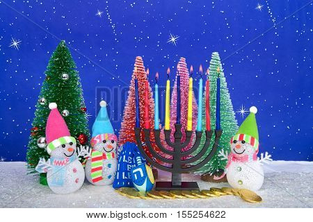 Menorah and red pink green pine trees with snowman on faux snow blue background white dots and stars. Christmas and Hanukkah together. Multi faith celebration.