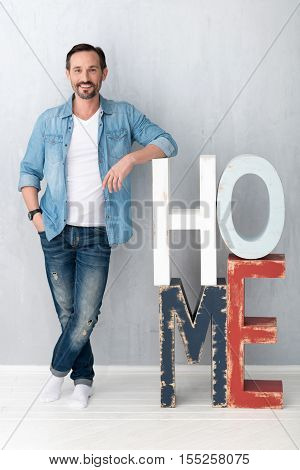 Great mood. Attractive handsome positive man standing near the letters HOME and smiling while being in a great mood