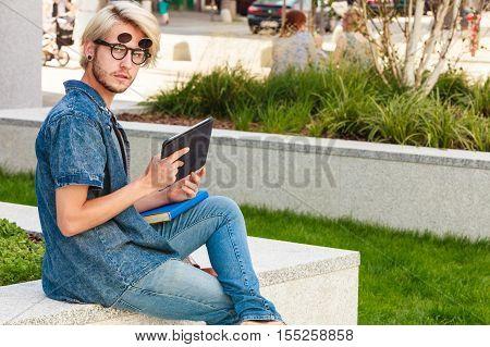 Hipster Guy With Tablet Sitting On Ledge