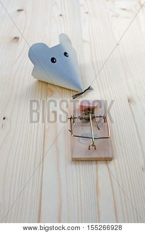 Mouse made of paper and mousetrap with bacon on wood.  good bait catches mice