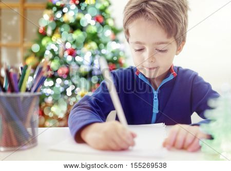 Child writing a Christmas list letter to Santa Claus
