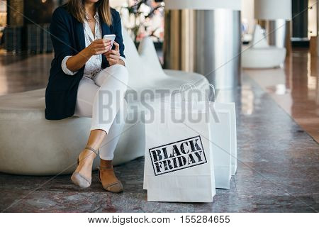 Black Friday. A person searching for something sitting in mall. Horizontal indoors shot.