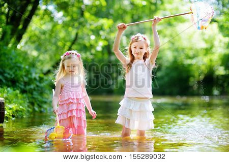 Two Cute Little Sisters Playing In A River Catching Rubber Ducks With Their Scoop-nets