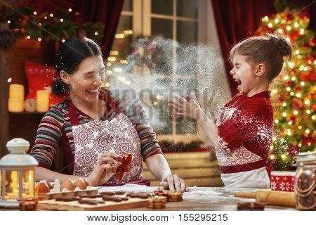 Merry Christmas and Happy Holidays. Family preparation holiday food. Mother and daughter cooking Christmas cookies.