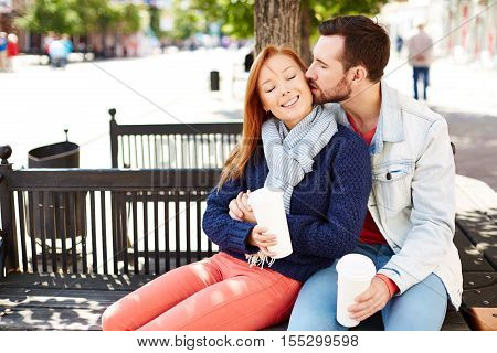 Adorable couple sitting on the bench in park, a man kissing a woman on the cheek