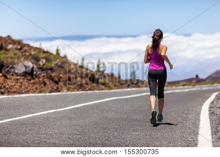 Outdoor fitness woman runner running on road. Sport athlete running woman runner jogging outdoor training for marathon race run. Young woman running outdoors working out cardio on nature landscape.