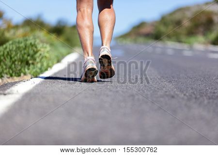 Road to success. Runner with determination running long distance endurance run on marathon race road. Closeup of legs and running shoes with copy space on path background. Man running shoes.