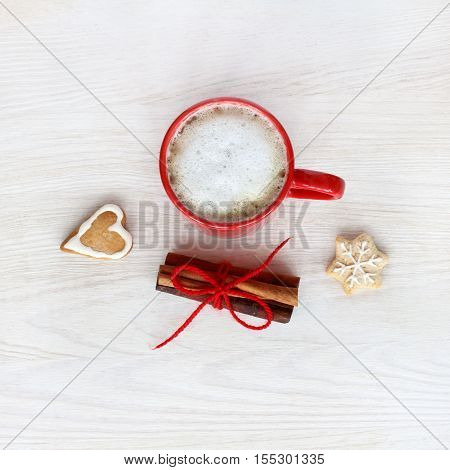 frothy coffee with gingerbread and cinnamon top view / drink with a festive mood