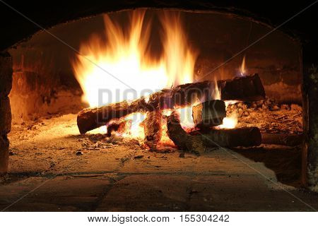 burning firewood in the fireplace retro / warming cozy atmosphere