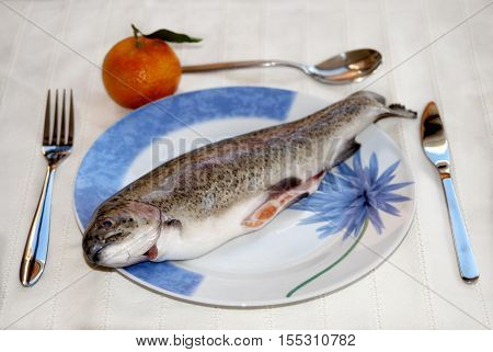 raw fresh trout in a dish on a set table