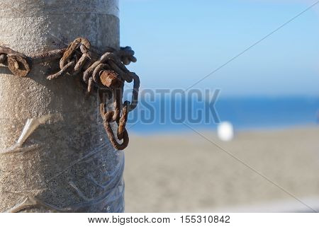 rusty chain stand out against the sea on a beach