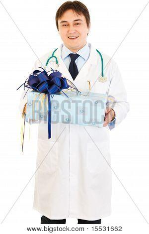 Lächelnd Arzt holding present in Händen, isolated on white